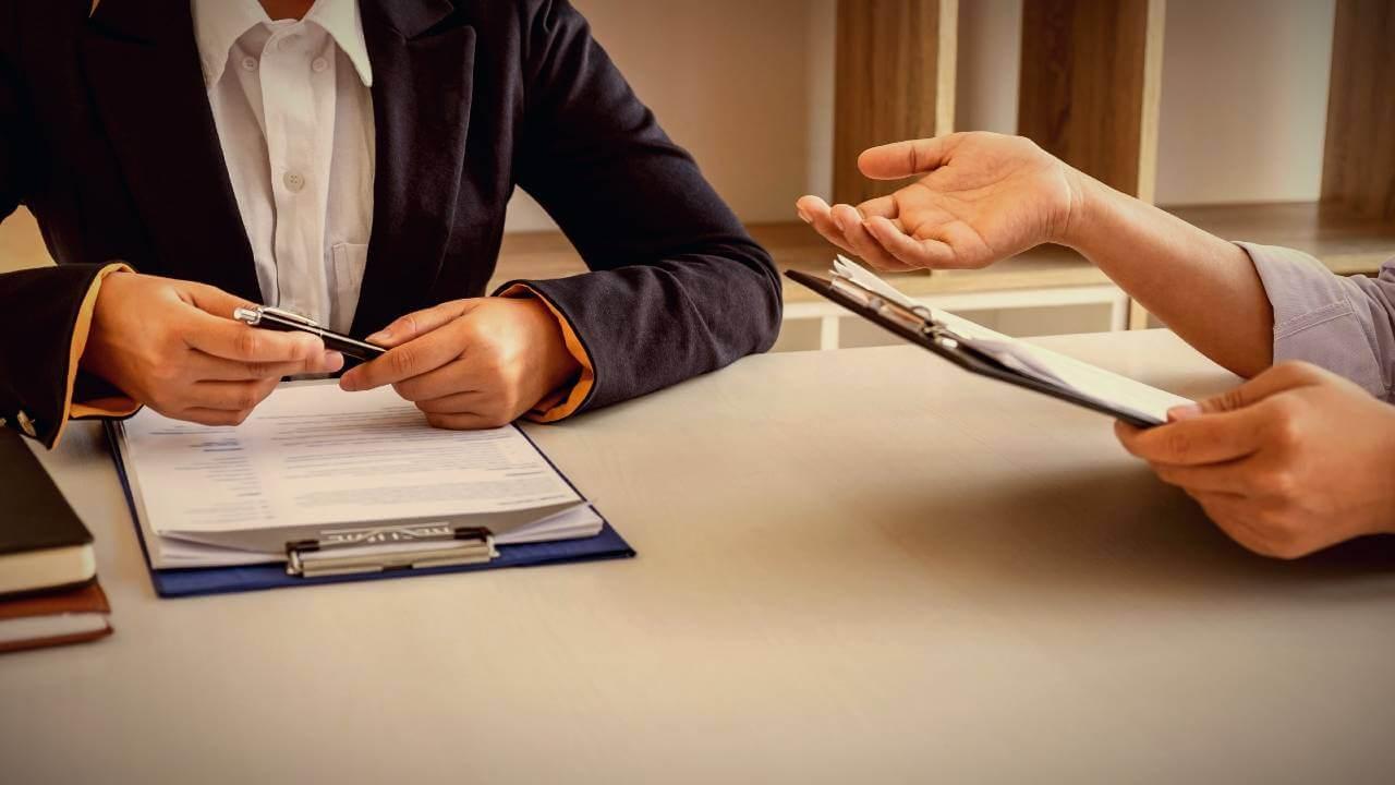 Dwie osoby siedzące przy stole podczas rozmowy rekrutacyjnej.