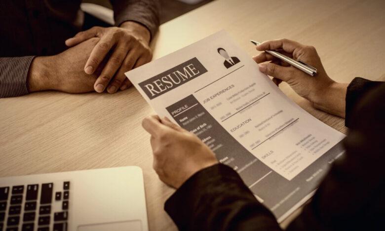 Rozmowa rekrutacyjna. Rekruter trzyma w ręce CV kandydata i zadaje mu pytania.