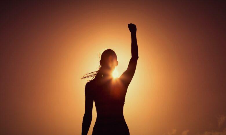 Kobieta na tle zachodzącego słońca z pięścią uniesioną do góry w geście zwycięstwa.